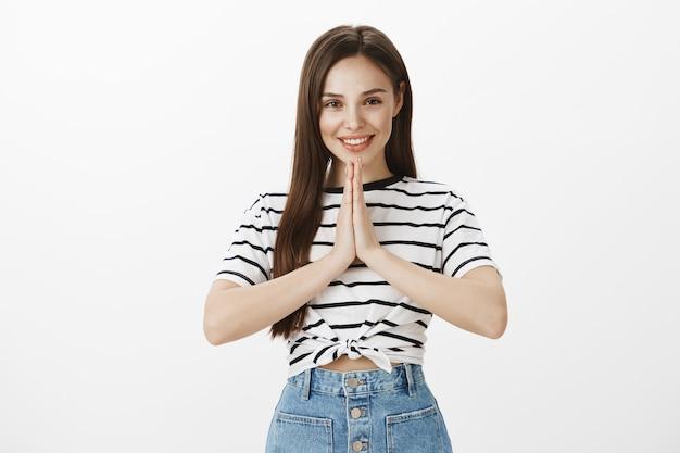 Espoir séduisante jeune femme tenant la main dans la mendicité, le geste de plaidoyer, demandant s'il vous plaît