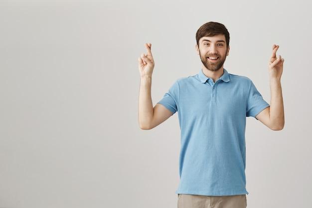 Espoir souriant jeune homme barbu posant