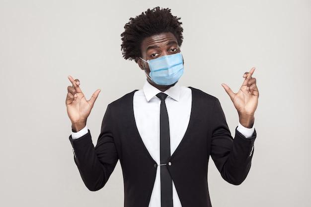 Espoir ou vœu. portrait d'inquiétude jeune bel homme ouvrier vêtu d'un costume noir avec masque médical chirurgical debout avec les doigts croisés et l'espoir. tourné en studio intérieur isolé sur fond gris.