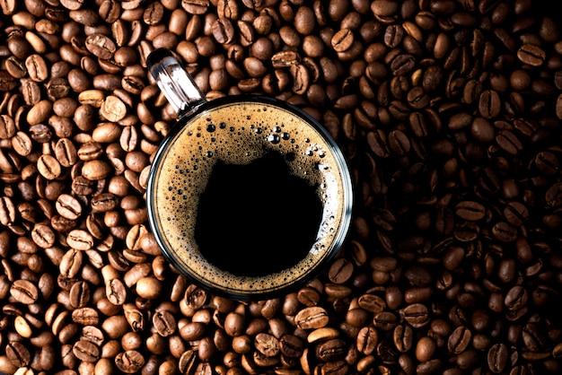 Espresso avec mousse de café dans une tasse de grains de café, vue de dessus, mise au point sélective, espace copie.