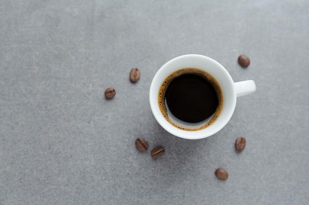 Espresso savoureux dans une tasse avec des grains de café. vue d'en-haut. table en béton.