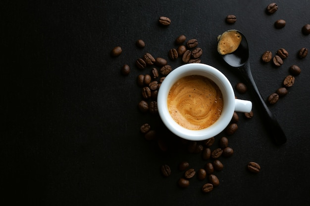 Espresso savoureux servi dans une tasse avec des grains de café autour et une cuillère. vue d'en-haut. fond sombre.