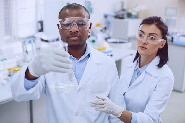 Esprit d'équipe. biologiste afro-américain déterminé effectuant un test et son collègue l'aidant