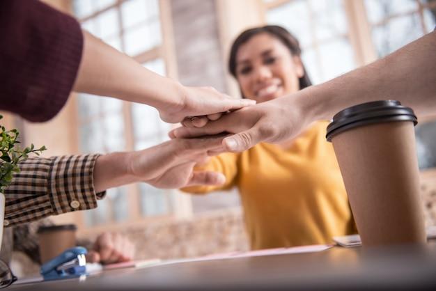 Esprit d'équipe. gros plan des mains de belles personnes positives en cours de mise en place tout en montrant leur esprit d'équipe