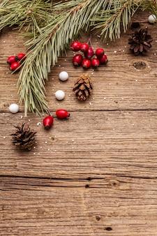 Esprit de noël sur table en bois. baies fraîches de rose de chien, bonbons en boule, branches et pommes de pin, neige artificielle. décorations nature, planches en bois vintage