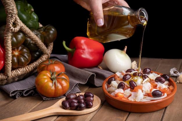 Esqueixada dans une casserole d'argile avec des ingrédients et une cuillère en bois avec des olives noires arrosées d'huile d'olive extra vierge.