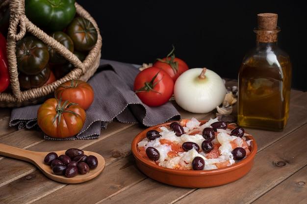 Esqueixada en pot d'argile et cuillère en bois avec quelques olives noires.