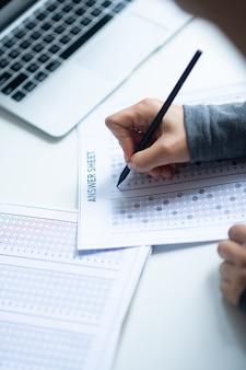 Essais de correction. vue de dessus d'un enseignant travailleur assis près d'un ordinateur portable corrigeant les tests des élèves