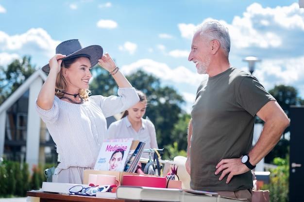 Essayer le chapeau. femme séduisante souriante essayant un chapeau de cowboy sombre lors d'une visite de vente de garage avec son agréable mari barbu