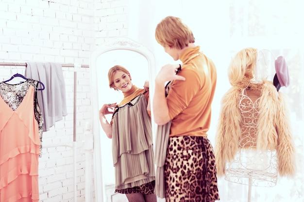 Essayer différentes tenues. belle grande transgenre passant du temps dans sa chambre à changer d'apparence