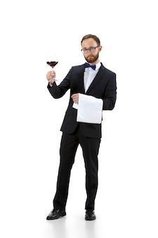 Essayer du vin rouge. portrait d'un sommelier masculin, d'un sommelier ou d'un employé de bar en costume blanc et noir isolé sur fond blanc. copyspace pour l'annonce. concept d'occupation professionnelle, emploi.