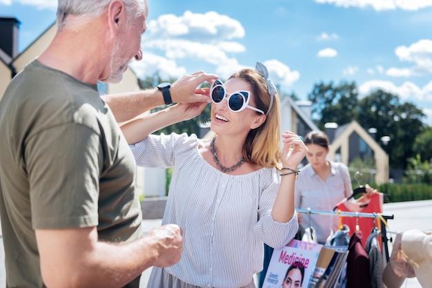 Essayer des lunettes de soleil. belle belle femme aux cheveux blonds portant un joli collier et bracelet essayant des lunettes de soleil