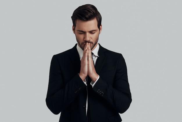 Essayer de trouver l'harmonie. beau jeune homme en costume complet gardant les mains jointes et les yeux fermés en se tenant debout sur fond gris