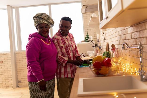 Essayez-le. ravie belle femme tenant un verre de vin tout en le donnant d'essayer à son mari