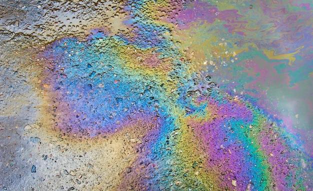 De l'essence sur l'asphalte, une grande flaque d'eau polluée.