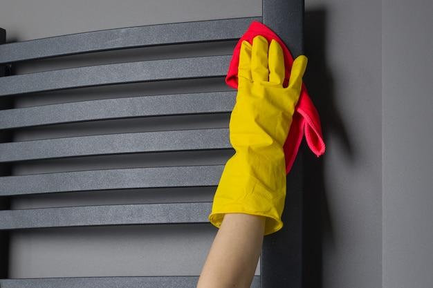 Essuie le radiateur de salle de bain avec un chiffon
