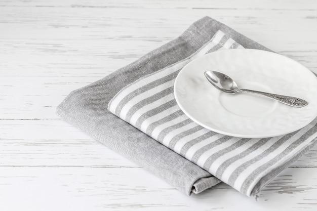 Essuie-tout gris sur une table en bois blanche avec une soucoupe et une cuillère