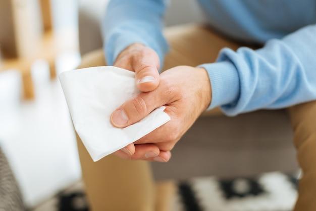 Essuyant ses larmes. gros plan d'un mouchoir en papier étant entre les mains d'un homme malheureux déprimé sans joie en pleurant