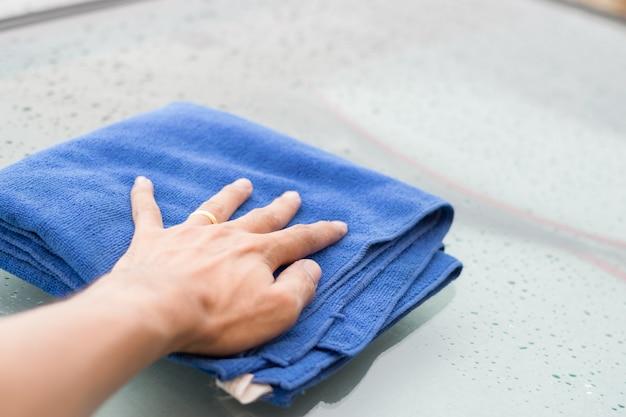 Essuyez les gouttes de pluie sur le toit de la voiture avec un chiffon en microfibre.