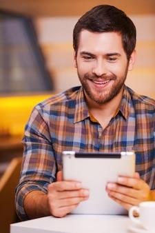C'est amusant. beau jeune homme regardant sa tablette numérique et souriant alors qu'il était assis dans un café