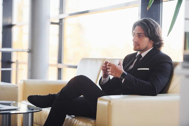 Est assis sur le canapé avec une tasse de boisson. portrait de beau jeune homme d'affaires en costume noir et cravate.