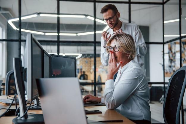 C'est un échec. deux courtiers en vêtements formels travaillent au bureau avec le marché financier.