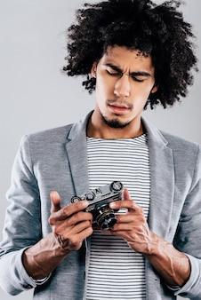 Où est l'écran numérique ici ? beau jeune homme africain tenant un appareil photo de style rétro et le regardant en se tenant debout