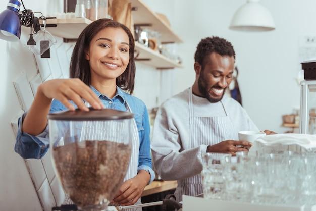 C'est en forgeant qu'on devient forgeron. belle jeune femme à l'aide d'une machine à café et faire du café pendant que son collègue masculin souriant le goûter
