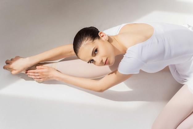 C'est en forgeant qu'on devient forgeron. vue de dessus de la belle jeune ballerine faisant des exercices d'étirement et regardant la caméra