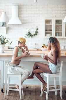C'est l'heure du café. deux jeunes copines jolies adultes de boire du café pieds nus à table de cuisine assis en face de l'autre parler