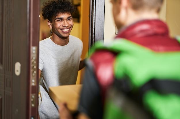 C'est l'heure de la pizza, un jeune homme qui a l'air heureux en rencontrant un coursier avec une boîte à pizza qui passe du temps à la maison