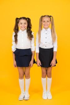 C'est important d'avoir des amis. heureux petits amis. petits amis de l'école souriant sur fond jaune. adorables amies profitant de leur amitié.