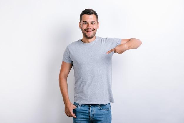 C'est moi! jeune homme ambitieux avec un sourire à pleines dents sur le visage pointant le doigt sur lui-même, adolescent confiant. studio intérieur tourné isolé sur fond blanc