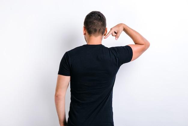 C'est moi. vue arrière du fier beau jeune homme debout et pointant sur lui-même. prise de vue en studio intérieur, isolé sur fond blanc