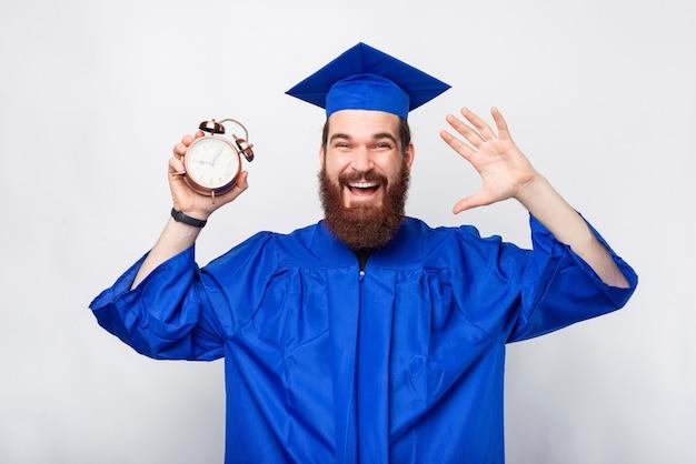 C'est le moment idéal pour obtenir son diplôme, un homme barbu portant une robe de graduation tient un réveil.