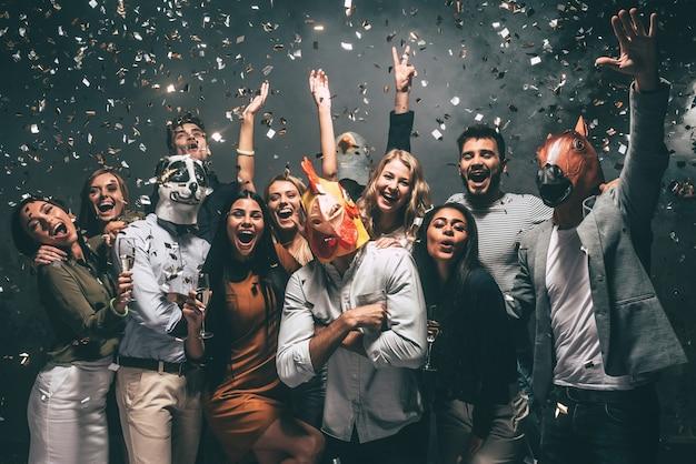 C'est mon année ! groupe de jeunes portant des masques d'animaux jetant des confettis et ayant l'air heureux