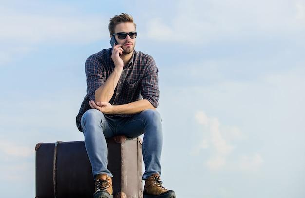 Ou est mon taxi. fond de ciel homme sexy parler au téléphone. style de mode masculin. l'air si tendance. homme d'affaires dans des verres. voyage d'affaires. macho man touriste relax tour sac. le voyageur attend le taxi. se déplacer.