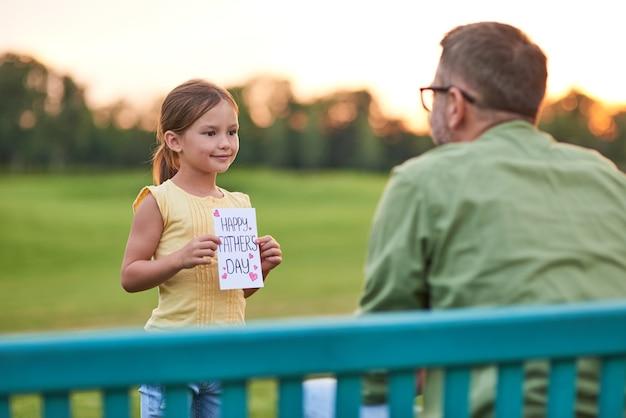 C'est pour vous papa mignonne petite fille saluant son papa et lui donnant des dépenses de carte postale à la main