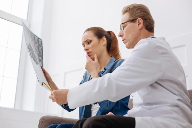 C'est le problème. excellent médecin professionnel déterminé expliquant à sa patiente pourquoi elle a besoin d'un traitement immédiat tout en s'assurant qu'elle comprend tout