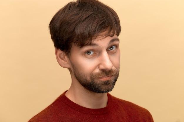 Est-ce que c'est. photo d'un jeune homme à la barbe portant un pull posant contre un mur beige