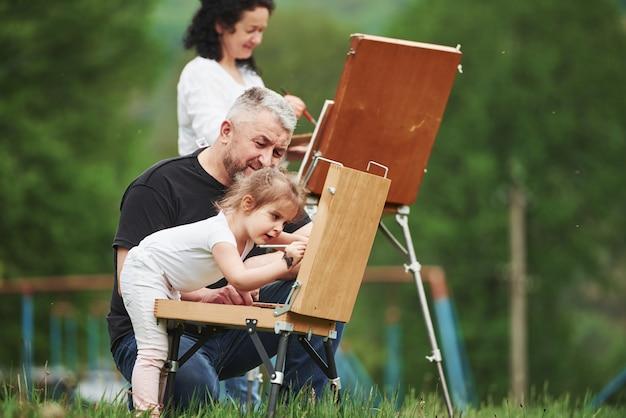Est-ce que je fais ça bien. grand-mère et grand-père s'amusent à l'extérieur avec leur petite-fille. conception de peinture