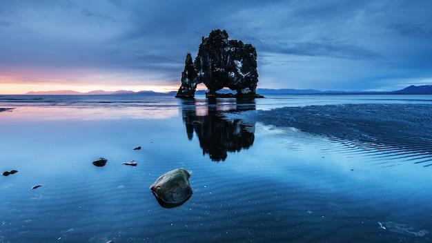 Est un rocher spectaculaire dans la mer sur la côte nord de l'islande. les légendes disent que c'est un troll pétrifié. sur ce hvitserkur se reflète dans l'eau de mer après le coucher du soleil de minuit
