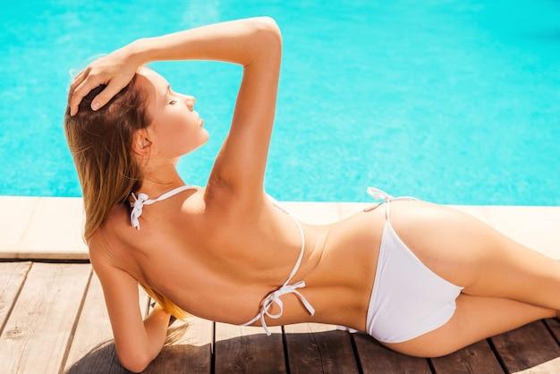 C'est son endroit d'été préféré. vue arrière de la belle jeune femme en bikini blanc allongé près de la piscine et tenant la main dans les cheveux