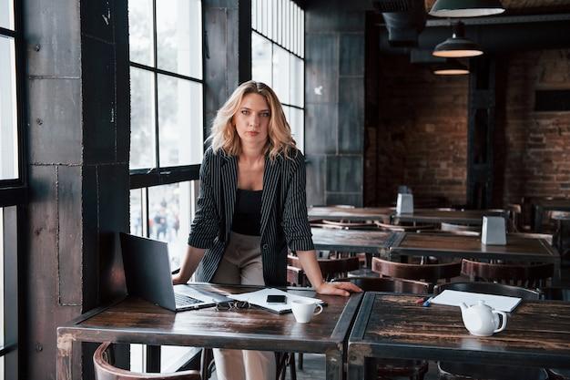 C'est son espace de travail pour aujourd'hui. femme d'affaires aux cheveux blonds bouclés à l'intérieur au café pendant la journée.