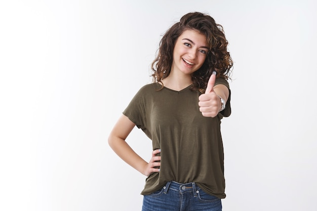 C'est super. portrait confiant insouciant sortant arménien jeune fille coiffure frisée show thumb up sûr de soi assertif souriant joyeusement applaudir aimer travail impressionnant fait, debout fond blanc