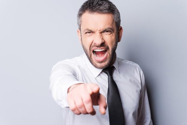 C'est de ta faute! homme mûr furieux en chemise et cravate criant et vous pointant en vous tenant debout sur fond gris