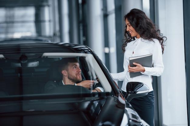 C'est à toi maintenant. client masculin et femme d'affaires moderne dans le salon automobile