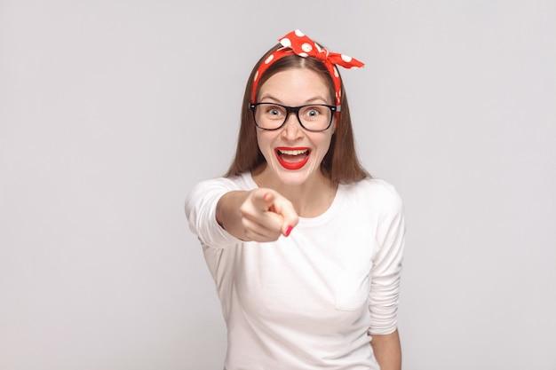 C'est toi ? pointer du doigt la caméra. portrait d'une belle jeune femme émotive en t-shirt blanc avec taches de rousseur, lunettes noires, lèvres rouges et bandeau. intérieur, isolé sur fond gris clair.