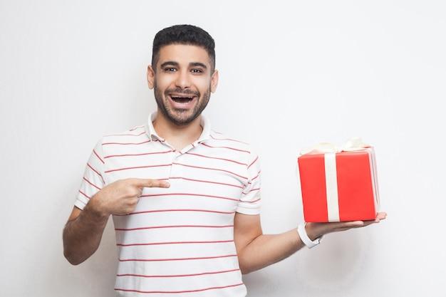 C'est à toi? satisfait beau jeune adulte moderne en t-shirt debout, tenant une grande boîte-cadeau avec la bouche ouverte, pointant le doigt, regardant la caméra. studio shot, fond blanc, isolé, intérieur
