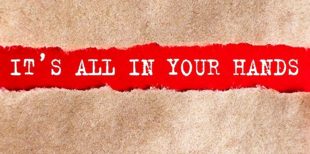 C'est tout dans vos mains mot écrit sous papier déchiré sur fond rouge, affaires